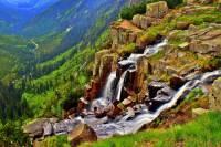 Voda Mumlavského vodopádu na obrázku č.14 padá z výšky cca 10 metrů. Voda vodopádu na obrázku č.15 padá po příkrých kaskádách do hlubin z úctyhodné výšky 148 metrů. Jak se vodopád na obrázku č.15, který je nejvyšším vodopádem v ČR jmenuje a na jakém chráněném území se nachází? (náhled)