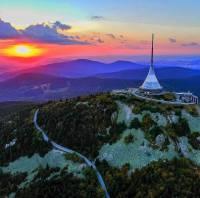 Hora Ještěd s hotelem a televizním vysílačem na fotografii č.17 se vypíná nad městem, jehož je dominantou a symbolem. Jak se město jmenuje? (náhled)